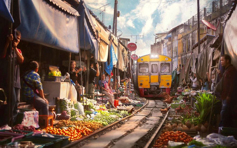 گذر از میان بازاری سرزنده و رنگارنگ با قطار در تایلند